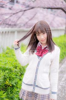 桜並木の前に立つ女子高生の写真・画像素材[858010]