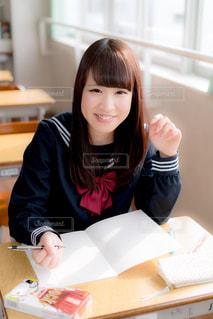 教室の机に座っている女子高生の写真・画像素材[858022]