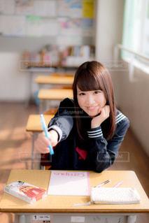 教室の机に座っている女子高生の写真・画像素材[858030]