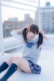 屋上でフェンスの横に座っている女子高生の写真・画像素材[858052]