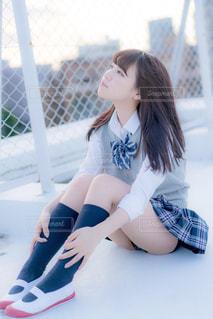 屋上でフェンスの前に座っている女子高生の写真・画像素材[858055]