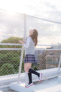 屋上で空を見上げる女子高生の写真・画像素材[858057]