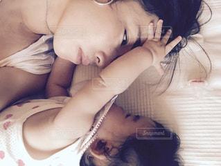 ベッドの上で横になっているママと赤ちゃんの写真・画像素材[725660]