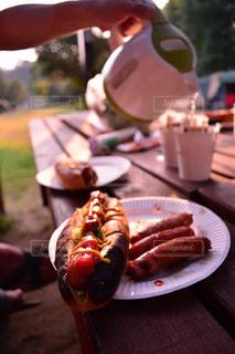 キャンプ場のテーブルの上に朝食のホットドッグの写真・画像素材[1215166]