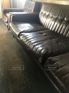 ベッドの上に座っている木製のベンチの行の写真・画像素材[1061650]