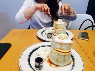 皿の上のケーキをテーブルに着席した人 - No.811921