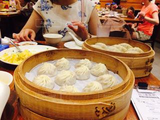 食物と一緒にテーブルに座って人の写真・画像素材[859467]