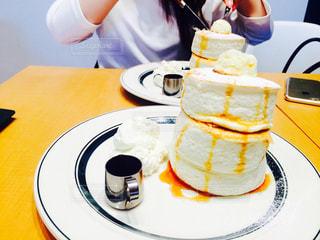 皿の上のケーキをテーブルに着席した人の写真・画像素材[868040]