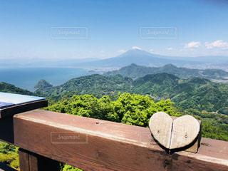 背景の山が付いている水の体の横にベンチの写真・画像素材[1194603]