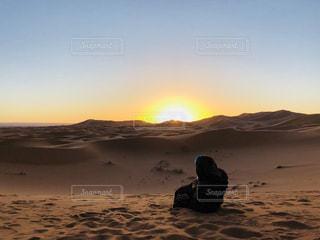 砂のビーチで夕日を持つ男の写真・画像素材[1194650]
