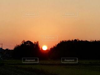 鮮やかなオレンジ色の空。山の凹みに夕日が落ちた😄の写真・画像素材[869524]