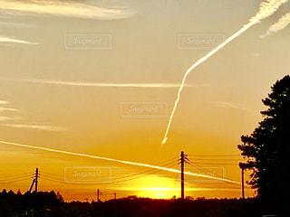 夕日と飛行機雲の写真・画像素材[1269309]