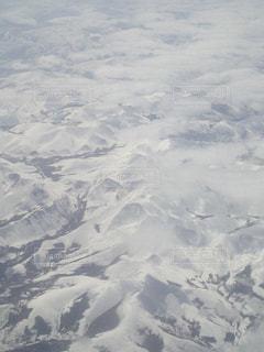 雪の覆われた山上空を飛ぶ飛行機 - No.911841