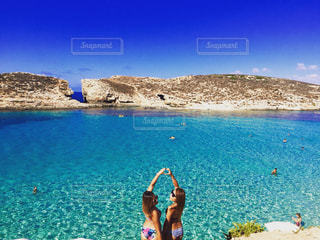 水の体の近くのビーチに空気を通って飛んで人の写真・画像素材[753306]