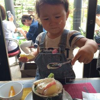 食品のプレートをテーブルに座っている少女の写真・画像素材[799811]