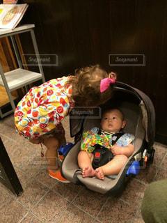 赤ちゃんの前に座っている少女 - No.816012
