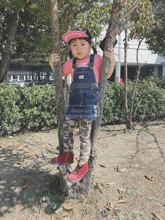 ツリーの横に立っている小さな男の子の写真・画像素材[1157668]