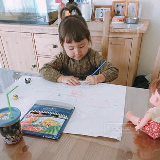 小さな女の子のテーブルに座っての写真・画像素材[1213305]