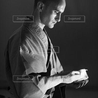 暗い部屋に立っている男の写真・画像素材[1261596]
