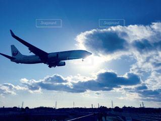 曇りの青い空を飛んでいるジェット大型旅客機の写真・画像素材[1313510]