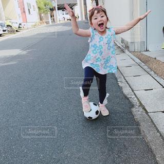 歩道にスケート ボードを保持している小さな女の子の写真・画像素材[1371217]
