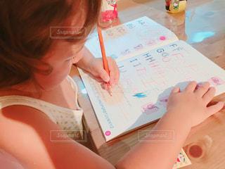 小さな女の子のテーブルに座っての写真・画像素材[1846075]