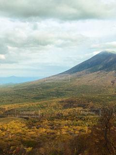 背景の山に大規模なグリーン フィールドの写真・画像素材[844204]