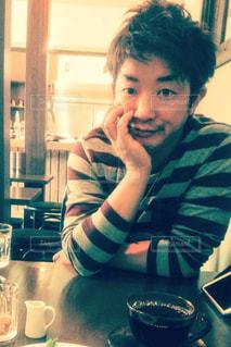 テーブルに肘をつく若い男性の写真・画像素材[1284964]