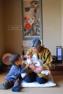 赤ちゃんを保持するテーブルに座っている人々 のグループの写真・画像素材[735617]
