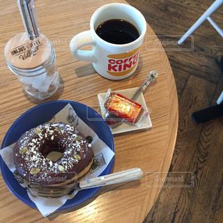 テーブルの上のコーヒー カップの隣に座ってドーナツ - No.804322
