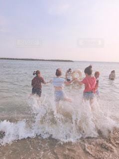 水の体の横に立っている人のグループの写真・画像素材[924299]