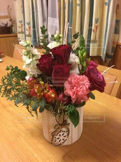 テーブルの上に座っての花で一杯の花瓶の写真・画像素材[945388]