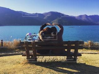 水の体の前でベンチに座っている女性の写真・画像素材[740968]