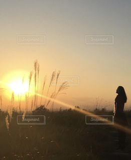 バック グラウンドで夕日を持つ人の写真・画像素材[1568042]