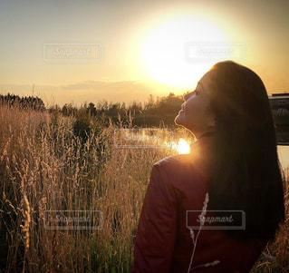 男の長い髪と背景の夕日の写真・画像素材[1685063]