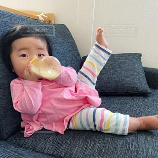 ソファでミルクを飲む赤ちゃんの写真・画像素材[3161028]