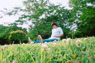 芝生に座ってお腹を撫でる妊婦の写真・画像素材[3167372]