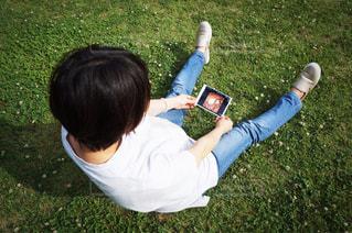 芝生の上でエコー写真を見る女性の写真・画像素材[3167373]