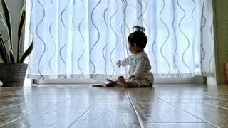 床に座ってカーテンを開けようとする赤ちゃんの写真・画像素材[3345415]