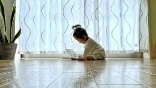床に座って絵本を読む赤ちゃんの写真・画像素材[3347455]