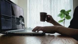 コーヒーを片手にパソコン作業の写真・画像素材[3356984]