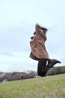 芝生でジャンプする女性の写真・画像素材[3461082]