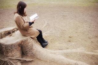 切り株に腰掛けて本を読む女性の写真・画像素材[3690834]