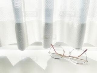 窓辺に置かれた眼鏡の写真・画像素材[3699923]