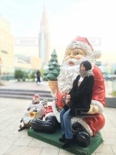 サンタクロースの像と写真を撮る女性の写真・画像素材[3841958]