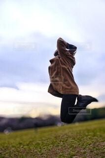 芝生の上でジャンプする女性の写真・画像素材[3853369]