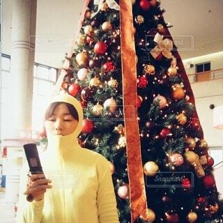クリスマスツリーの前で全身タイツを来た人が携帯電話をいじっているところの写真・画像素材[3979660]