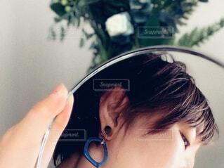 鏡に映るイヤリングをした女性の横顔の写真・画像素材[4318508]