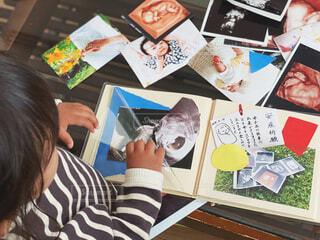 たくさんの写真とアルバムと子どもの写真・画像素材[4321833]