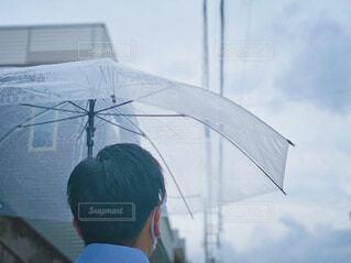 曇天とビニール傘をさす男性の後ろ姿の写真・画像素材[4560887]